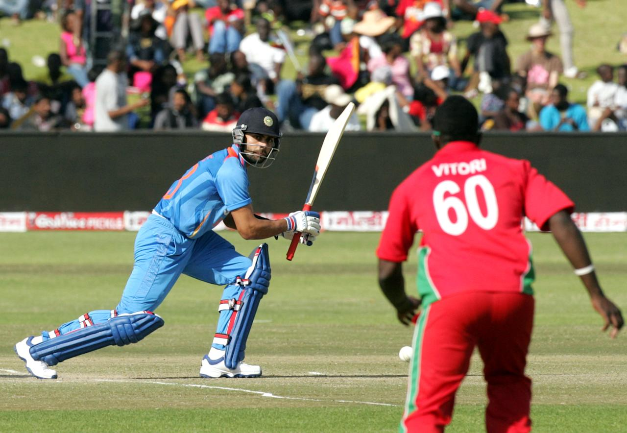 India's captain Virat Kohli (L) is seen in action during the 3rd match of the 5 cricket ODI series between Zimbabwe and India at Harare Sports Club on July 28, 2013. AFP PHOTO / JEKESAI NJIKIZANA        (Photo credit should read JEKESAI NJIKIZANA/AFP/Getty Images)