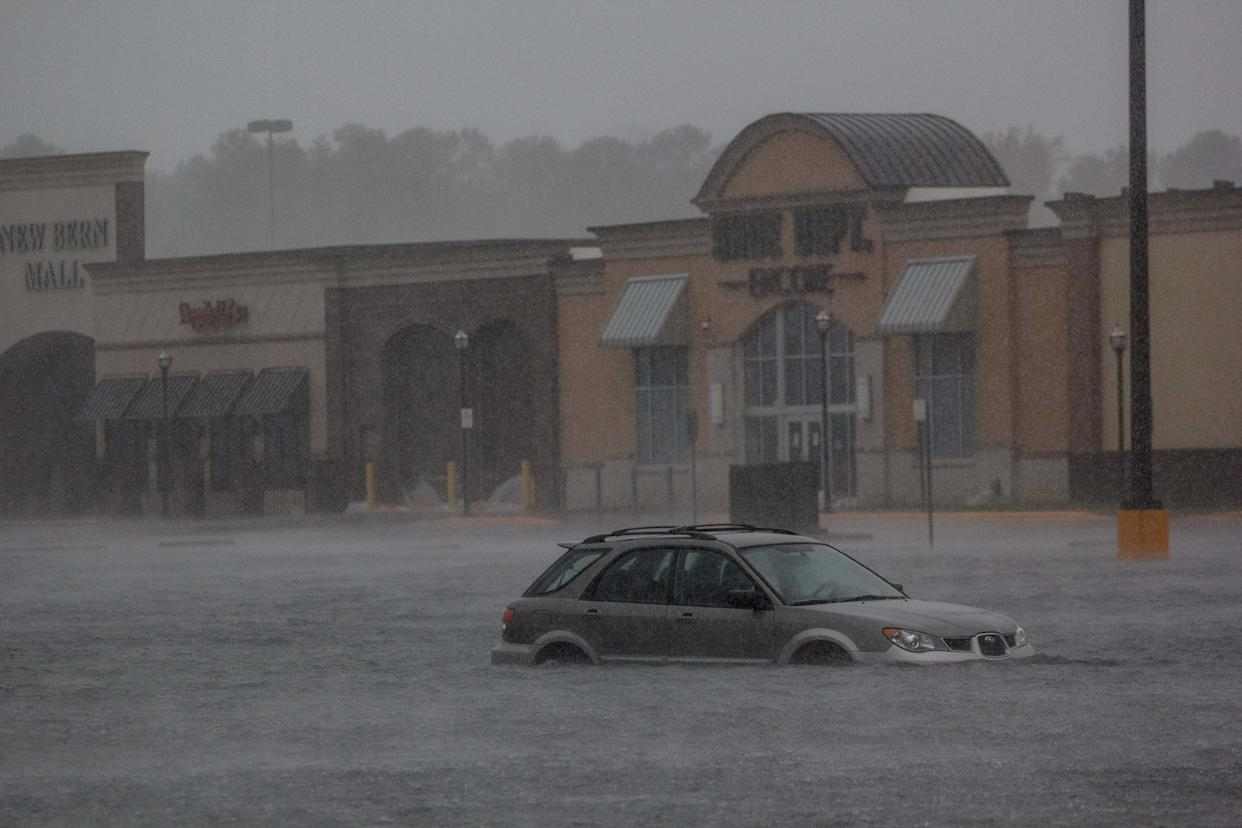 A car is seen in a flooded parking lot outside New Bern Mall in New Bern.