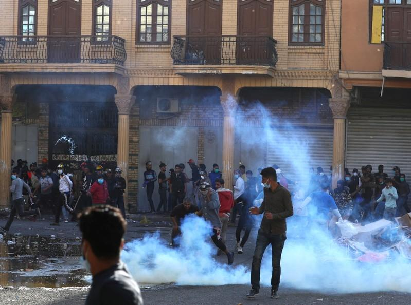 Demonstrators run from tear gas during ongoing anti-government protests in Baghdad