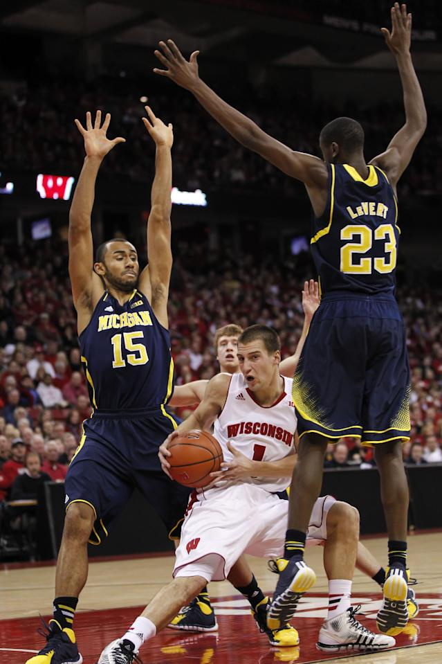 Wisconsin's Ben Brust, (1) is trapped by Michigan's Jon Horford (15) Spike Albrecht, back center, and Caris LeVert during the second half of an NCAA college basketball game Saturday, Jan. 18, 2014, in Madison, Wis. Michigan beat Wisconsin 77-70. (AP Photo/Andy Manis)