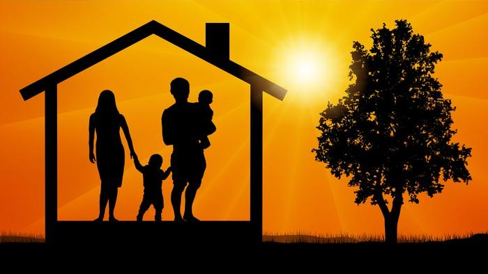 Stylized silhouette of young family inside a house frame set against a bright sun