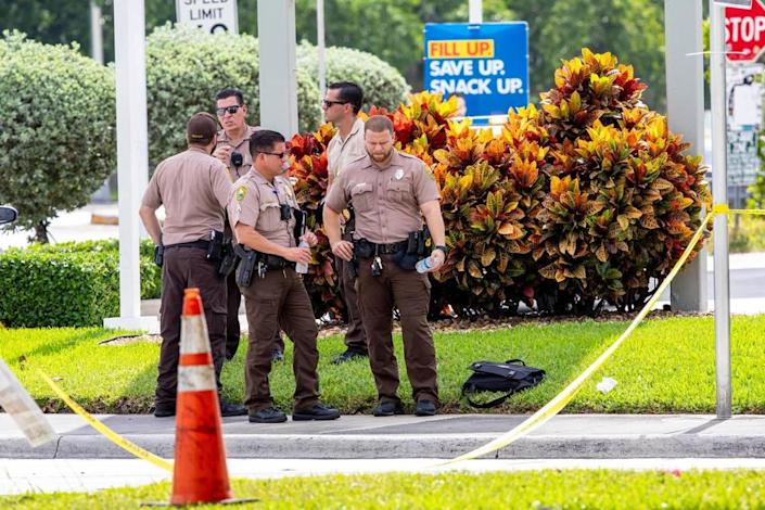 Miami-Dade Police officers and detectives gather outside the Shell gas station near the crime-scene after another Miami-Dade mass shooting and a possibly connected car crash killed three people and sent five or six others to the hospital with gunshot wounds, around Grand Salon Reception Hall at Southwest 104th Street and 109th Court in the Kendall neighborhood of Miami, Florida, on Sunday, June 6, 2021.