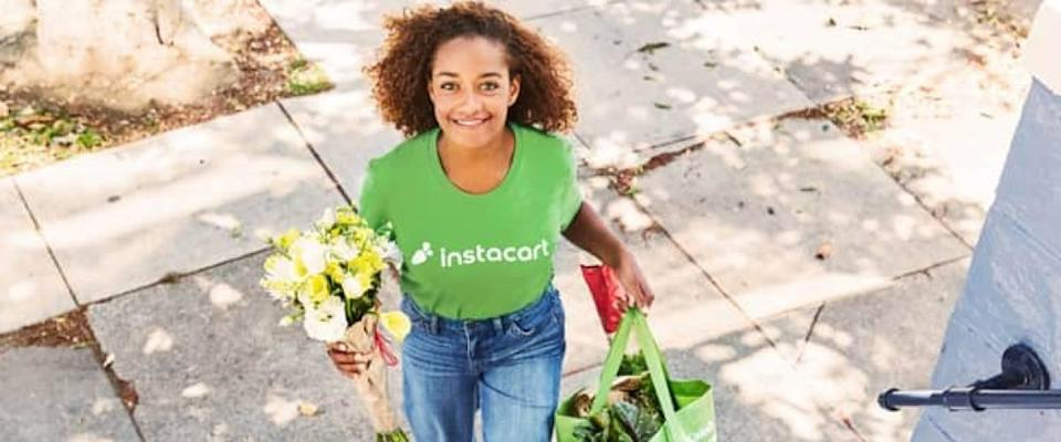 woman wearing instacart tshirt walks with bag of groceries and