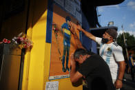 Fans mourn in front of a poster of Diego Maradona at the entrance of the Boca Juniors stadium, known as La Bombomera, in Buenos Aires, Argentina, Wednesday, Nov. 25, 2020. The Argentine soccer great who was among the best players ever and who led his country to the 1986 World Cup title before later struggling with cocaine use and obesity, died from a heart attack on Wednesday at his home in Buenos Aires. He was 60. (AP Photo/Natacha Pisarenko)