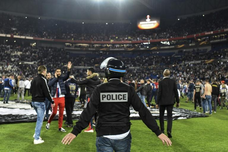 Police stand on the pitch after Besiktas' and Lyon's supporters fought before the UEFA Europa League first leg quarter final football match April 13, 2017, at the Parc Olympique Lyonnais stadium in Decines-Charpieu
