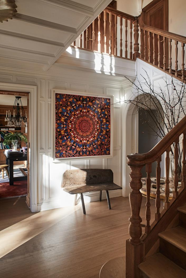 """<div class=""""caption""""> In the light-filled foyer, a Damien Hirst painting hangs over a primitive bench. </div>"""