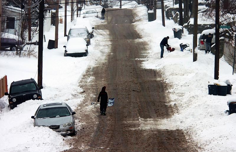 Residents with shovels and snow blowers start to clear out the snow along 8th Avenue in Carbondale, Pa. on Wednesday, Feb. 5, 2014 after the a snowstorm hit the area. (AP Photo/Scranton Times & Tribune, Butch Comegys) WILKES BARRE TIMES-LEADER OUT; MANDATORY CREDIT