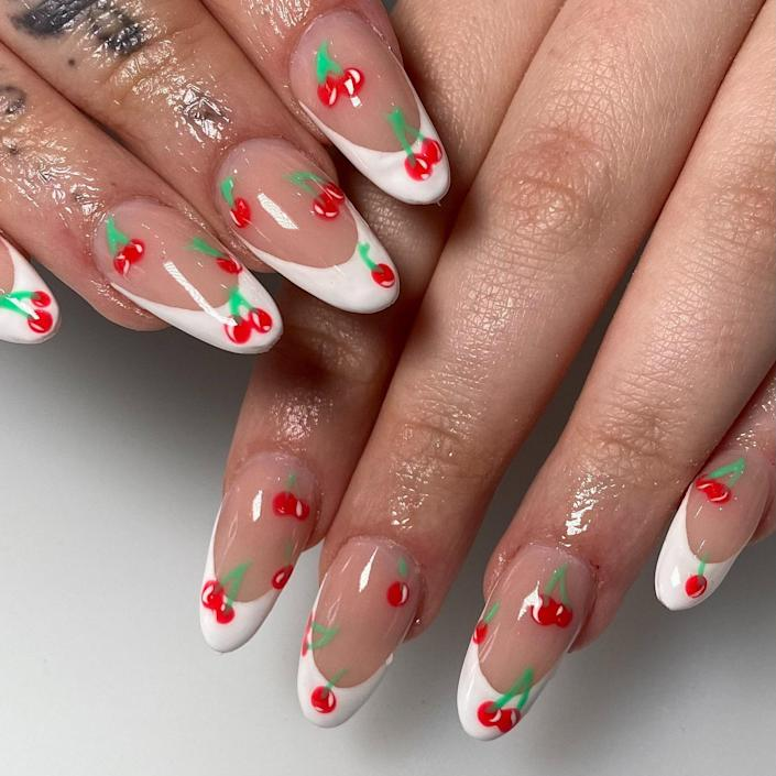 """Another French manicure — but this time on an oval-shaped set. U.K.-based manicurist <a href=""""https://www.instagram.com/_nailsbyelisha/"""" rel=""""nofollow noopener"""" target=""""_blank"""" data-ylk=""""slk:Elisha Emilius"""" class=""""link rapid-noclick-resp"""">Elisha Emilius</a> created a white, C-curve tip for these medium-length nails. With a dotting tool and a fine detail brush, she added dots of red polish to form the cherries and lines of green for the stems."""