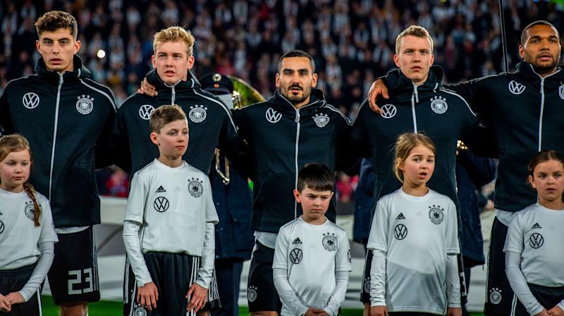 (L-R) Germany's midfielder Kai Havertz, Germany's forward Julian Brandt, Germany's captain Ilkay Gundogan, Germany's defender Lukas Klostermann and Germany's defender Jonathan Tah stand during the anthems prior to the friendly football match Germany v Serbia in Wolfsburg, western Germany on March 20, 2019. (Photo by John MACDOUGALL / AFP) / RESTRICTIONS: ACCORDING TO DFB RULES IMAGE SEQUENCES TO SIMULATE VIDEO IS NOT ALLOWED DURING MATCH TIME. MOBILE (MMS) USE IS NOT ALLOWED DURING AND FOR FURTHER TWO HOURS AFTER THE MATCH. == RESTRICTED TO EDITORIAL USE == FOR MORE INFORMATION CONTACT DFB DIRECTLY AT +49 69 67880 / (Photo credit should read JOHN MACDOUGALL/AFP/Getty Images)