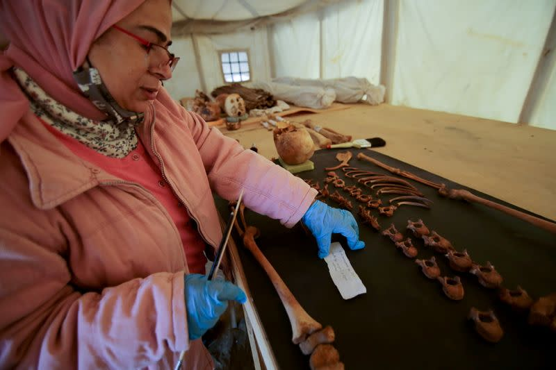 A woman works on artefacts, part of a recent discovery, at the Saqqara necropolis south of Cairo
