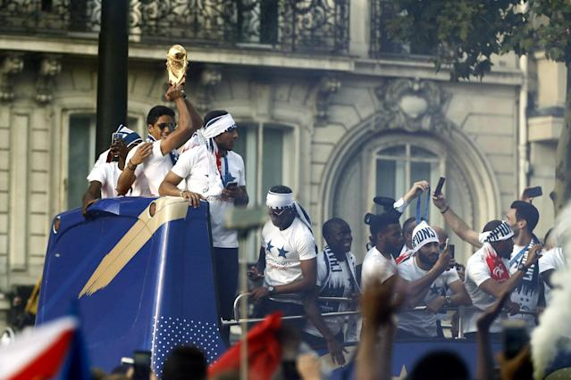 BOR129. Paris (France), 16/07/2018.- France's defender Raphael Varane (C) holds the trophy as he celebrates with teammates on the roof of a bus while parading down the Champs-Elysee avenue in Paris, France, 16 July 2018. France won 4-2 the FIFA World Cup 2018 final against Croatia in Moscow, on 15 July. (Croacia, Mundial de Fútbol, Moscú, Francia) EFE/EPA/GUILLAUME HORCAJUELO