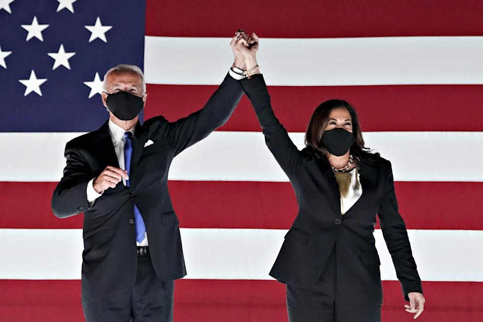 Former Vice President Joe Biden, Democratic presidential nominee, left, and Senator Kamala Harris, Democratic vice presidential nominee, wear protective masks while holding hands outside the Chase Center during the Democratic National Convention in Wilmington, Delaware, U.S., on Thursday, Aug. 20, 2020. (Stefani Reynolds/Bloomberg via Getty Images)