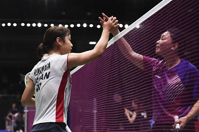 Nozomi Okuhara (L) of Japan shakes hands with Louisa Ma of Australia after their women's singles round one match at the Thomas and Uber cups badminton tournament in Bangkok on May 20, 2018. (AFP Photo/Lillian SUWANRUMPHA)