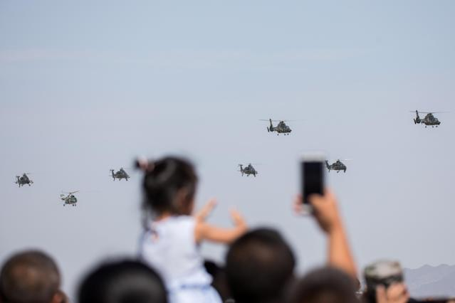 <p>Spectators take photos as helicopters perform during the opening ceremony of three games hosted by Chinese People's Liberation Army (PLA), part of International Army Games 2018 in Korla, Xinjiang Uighur Autonomous Region, China, July 29, 2018. (Photo: Stringer/Reuters) </p>