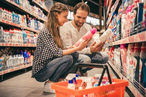 Two people compare detergents in a supermarket aisle.