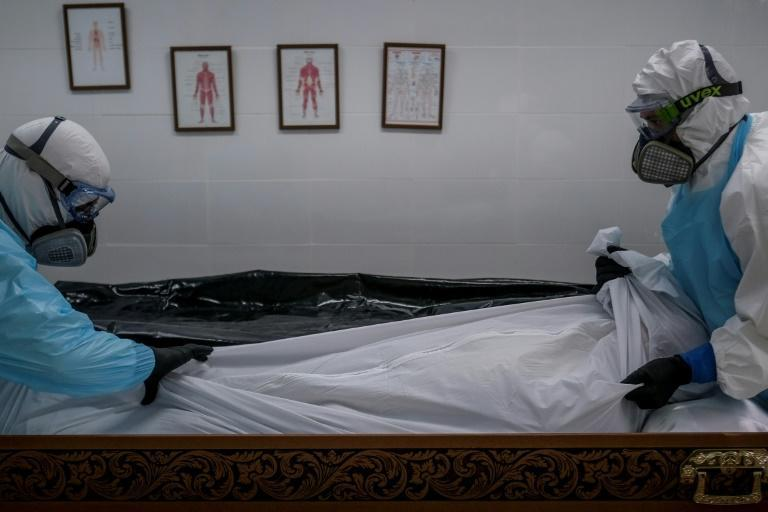 Staff in protective gear place the body of a Covid victim into a casket