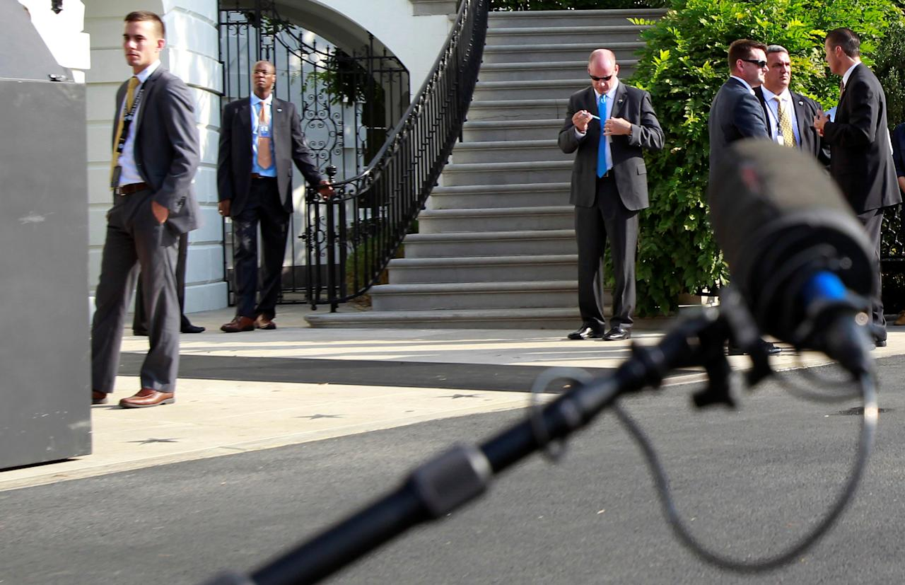 A TV microphone is seen with U.S. Secret Service agents behind before Marine One with U.S. President Barack Obama on board departs the White House in Washington, U.S. en route to Miami, October 20, 2016.  REUTERS/Yuri Gripas