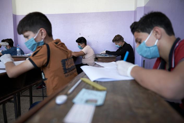 Syrian students in Idlib province take the middle school exam while maintaining safety procedures on July 12.