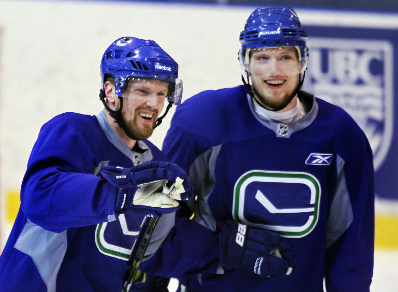 Vancouver Canucks center Henrik Sedin, left, and defenseman Christian Ehrhoff talf after a drill during practice for the NHL hockey Stanley Cup Finals, Friday, June 3, 2011, in Vancouver, British Columbia. The Canucks host the Boston Bruins in Game 2 of the best-of-seven games series on Saturday. The Canucks lead 1-0. (AP Photo/Julie Jacobson)