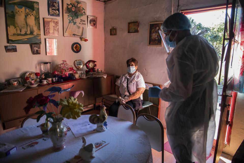 Health worker Adrian Hernandez, right, helps Isadora Davila after she returned home from a hospital in Salto, where she was treated for COVID-19, in Belen, Uruguay, Wednesday, April 28, 2021. (AP Photo/Matilde Campodonico)
