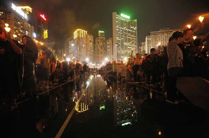 Tens of thousands of people attend a candlelight vigil under heavy rain at Hong Kong's Victoria Park in Hong Kong Tuesday June 4, 2013 to mark the 24th anniversary of the June 4th Chinese military crackdown on the pro-democracy movement in Beijing. (AP Photo/Vincent Yu)