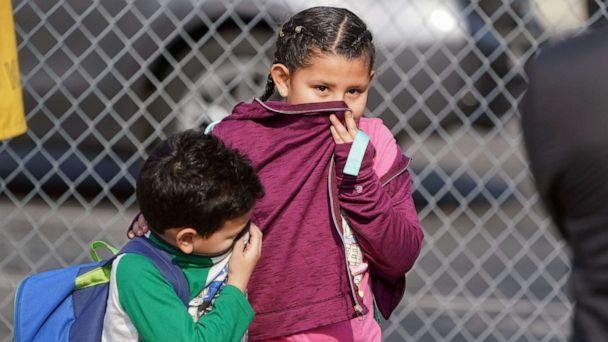 PHOTO: Children cover their noses and mouths while leaving school where 26 people were treated for jet fuel exposure at Park Avenue Elementary School in Cudahy, Calif., Jan. 14, 2020. (Scott Varley/Orange County Register via ZUMA Wire via Newscom)