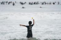 "Nathan Rangel, 11, jumps in the water carrying a rose as surfers participate in a paddle out ceremony at ""The Ink Well,"" a beach historically known as a surfing refuge for African Americans, to honor the life of George Floyd on Friday, June 5, 2020, in Santa Monica, Calif. Floyd died after he was restrained in police custody on Memorial Day in Minneapolis. (AP Photo/Ashley Landis)"