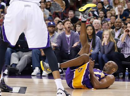 Kobe Bryant goes to the ground during the second quarter of the Lakers' loss to the Kings on Sunday. (USAT)