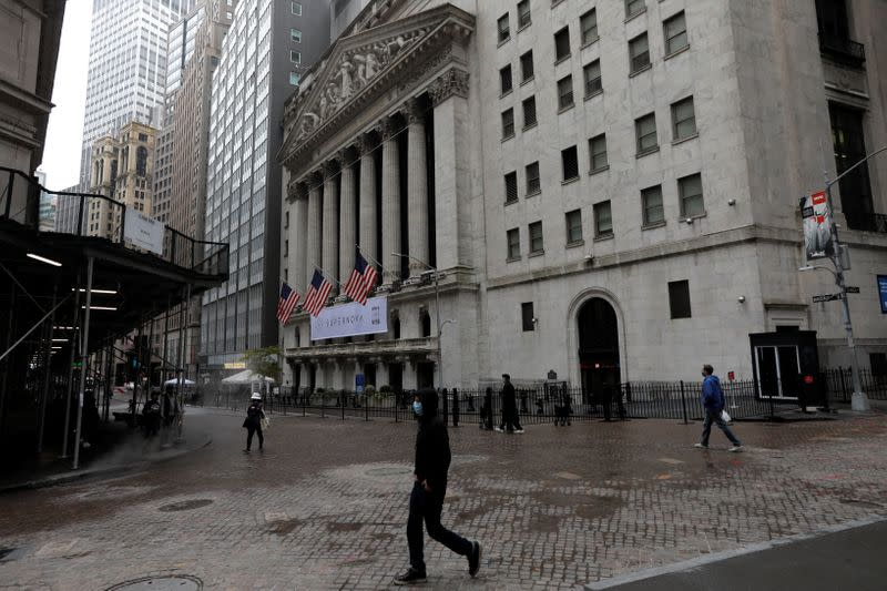 People wearing protective face masks walk outside New York Stock Exchange in New York