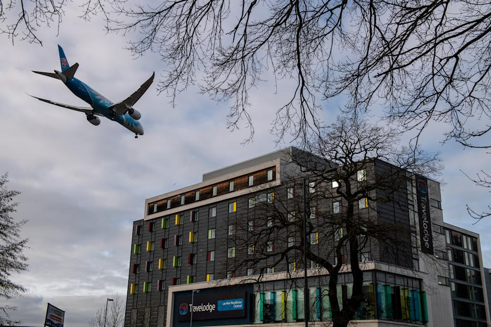 "LONDON, ENGLAND - JANUARY 28: An airplane flies over a Travelodge Hotel as it comes in to land at Heathrow Airport on January 28, 2021 in London, England. Arriving travellers from 22 ""red list"" countries including South Africa, South American countries and Portugal, will now need to quarantine in hotel rooms upon arrival to the UK. The measures have been introduced to prevent new strains of the covid-19 virus from taking hold here. Other countries have adopted this policy with travellers paying for their accommodation in designated hotels and are delivered meals during the quarantine period. (Photo by Chris J Ratcliffe/Getty Images)"