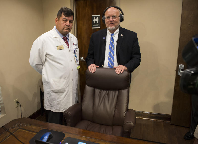 CDC director Robert Redfield, right, tests out the bluetooth stethoscope inside a telemedicine room at the Medical Advocacy and Outreach clinic in Montgomery, Ala. on Friday, June 14, 2019. (Jake Crandall/Montgomery Advertiser via AP)
