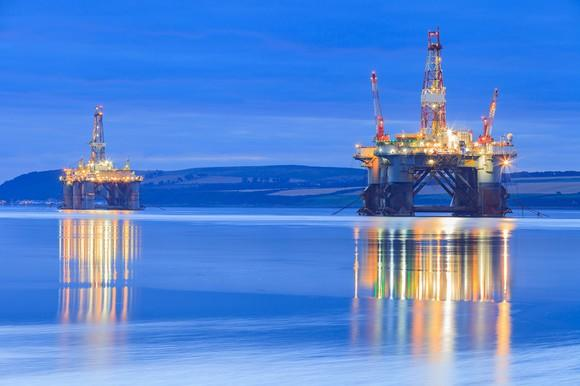 Two semisubmersible drilling rigs at night.