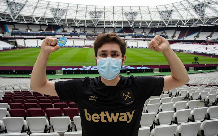 West Ham fan Daniel Hearn, 25, celebrates after having his first jab at the club's London Stadium,where 15,000 doses were available on Saturday - Jamie Lorriman