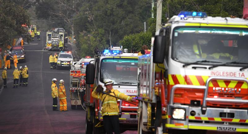 Line of NSW RFS firetrucks fighting bushfire in South Turramurra.
