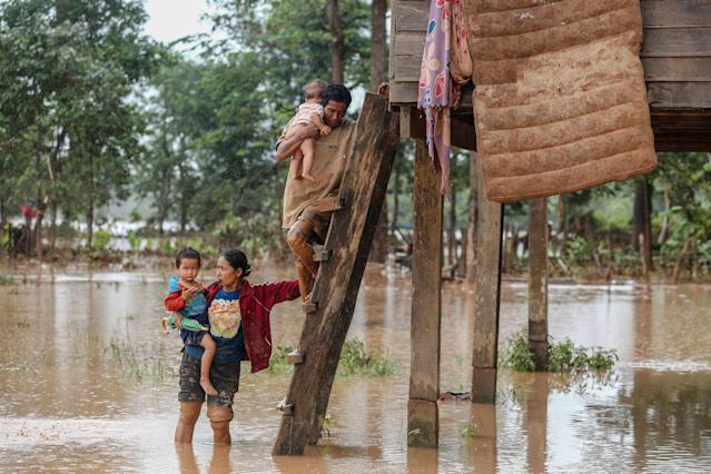 <p>A couple carry their children from their home in the flooded area in Sanamxai, Attapeu province, on July 26, 2018. (Photo: Kao Nguyen/AFP/Getty Images) </p>