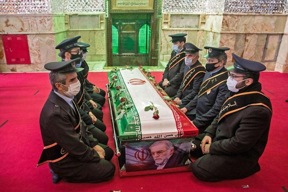 Members of Iranian forces pray around the coffin of nuclear scientist Mohsen Fakhrizadeh (TASNIM NEWS/AFP via Getty Images)