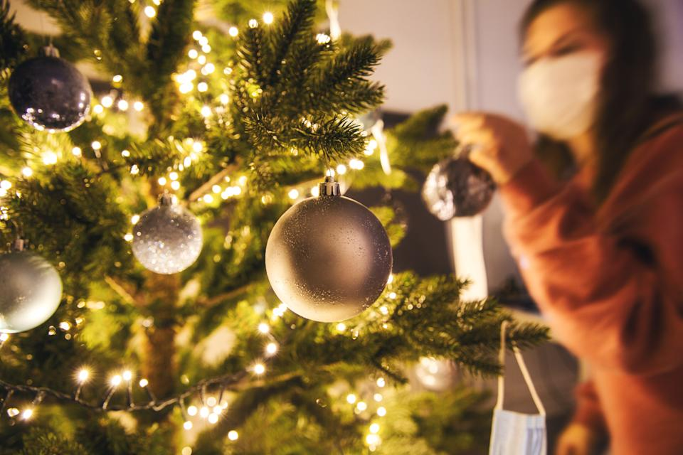 Young woman decorating a Christmas tree with medical safety mask for Covid-19, Coronavirus and Christmas concept, beautiful holiday background