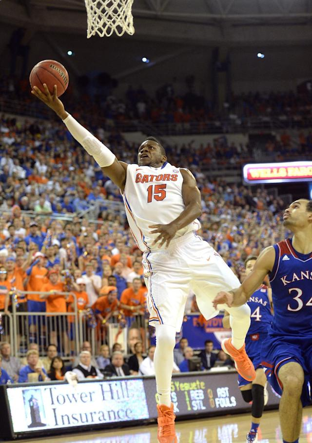 Florida forward Will Yeguete (15) goes to the basket for two points as Kansas forward Perry Ellis (34) is unable to block the shot during the first half of an NCAA college basketball game Tuesday, Dec. 10, 2013 in Gainesville, Fla. (AP Photo/Phil Sandlin)