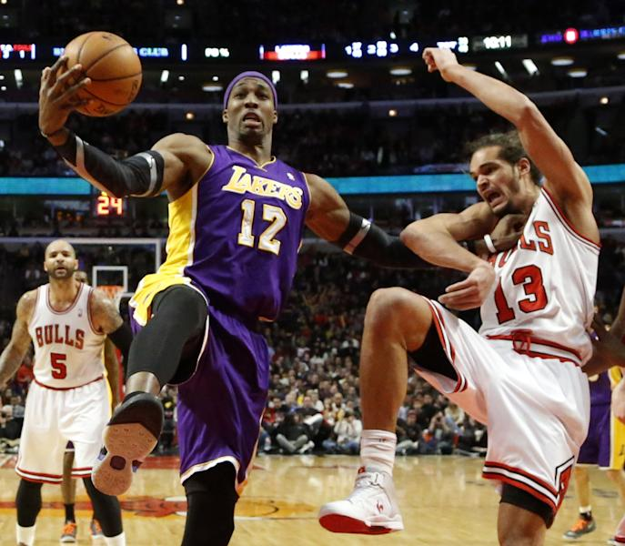Los Angeles Lakers center Dwight Howard (12) pushes Chicago Bulls center Joakim Noah (13) away from a rebound during the second half of an NBA basketball game Monday, Jan. 21, 2013, in Chicago. The Bulls won 95-83. (AP Photo/Charles Rex Arbogast)