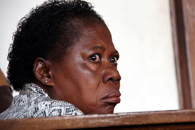 "In this photograph taken on Thursday, March 20, 2014, a Ugandan nurse, Rosemary Namubiru, sits in court in the capital Kampala, Uganda. She is accused of injecting a two year old boy Mathew Mushabe with HIV/Aids virus. Goaded by journalists who wanted a clear view of her face, the Ugandan nurse looked dazed and on the verge of tears. The Ugandan press had dubbed her ""the killer nurse"" after the HIV-infected medical worker was accused of deliberately injecting her blood into a two-year-old patient. (AP Photo)"