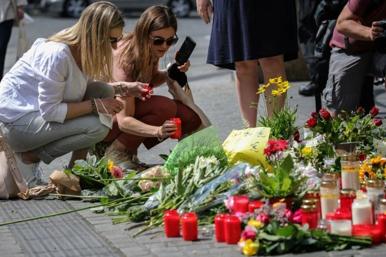 Two women place a candle at a makeshift memorial where a man went on a stabbing spree in the Germany city of Wuerzburg
