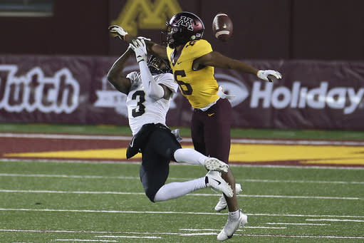 Purdue wide receiver David Bell (3) misses a pass next to Minnesota defensive back Miles Fleming (6) during the first half of an NCAA college football game Friday, Nov. 20, 2020, in Minneapolis. (AP Photo/Stacy Bengs)