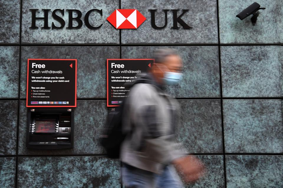 """A pedestrian wearing a face mask or covering due to the COVID-19 pandemic, walks past a branch of a HSBC bank in central London on August 3, 2020. - HSBC on Monday revealed a 69-percent slump in net profits, joining a number of major bank whose earnings have been slammed by coronavirus fallout. HSBC announced """"reported profit after tax"""" of $3.1 billion (2.6 billion euros) compared with almost $10 the first six months of 2019, with spiralling China-US tensions also hurting the Asia-focused lender. (Photo by DANIEL LEAL-OLIVAS / AFP) (Photo by DANIEL LEAL-OLIVAS/AFP via Getty Images)"""
