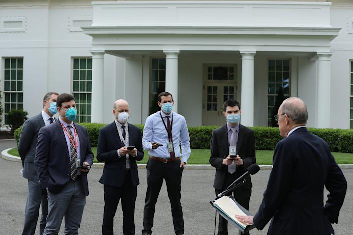 Reporters wear face masks to interview Larry Kudlow, director of the White House Economic Council, outside the West Wing.