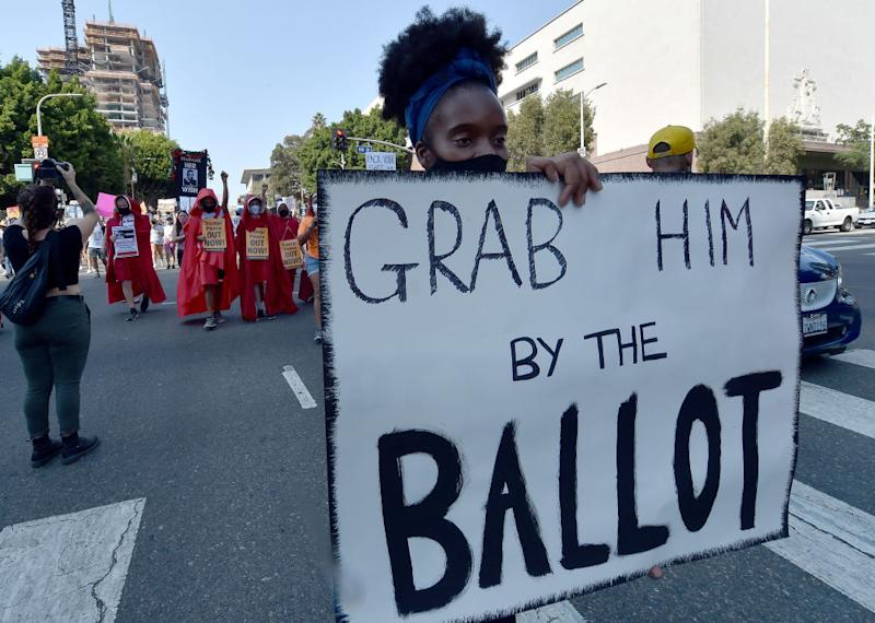 """Female protester holding up """"Grab him by the ballot"""" sign"""