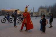 A performer dressed as the monkey god from a Chinese fable walks near a mosque as Uyghur children gaze upon him Kashgar in northwestern China's Xinjiang Uyghur Autonomous Region on Friday, March 19, 2021. Four years after Beijing's brutal crackdown on largely Muslim minorities native to Xinjiang, Chinese authorities are dialing back the region's high-tech police state and stepping up tourism. But even as a sense of normality returns, fear remains, hidden but pervasive. (AP Photo/Ng Han Guan)