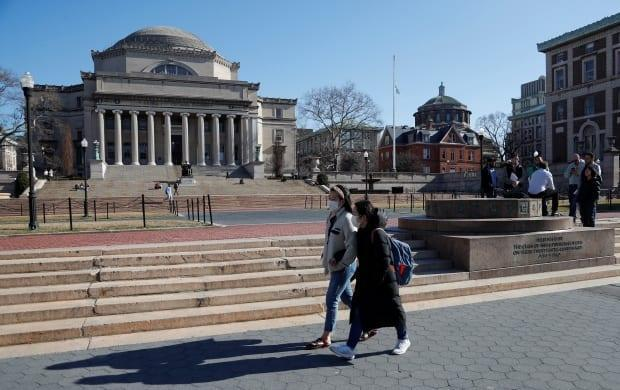 People wear face masks at Columbia University in New York City last year. Some parents in Canada worry about whether they'll be able to take their children across the border to school after it was announced that the U.S. land border will remain closed to non-essential travel until at least Aug. 21. (Shannon Stapleton/Reuters - image credit)