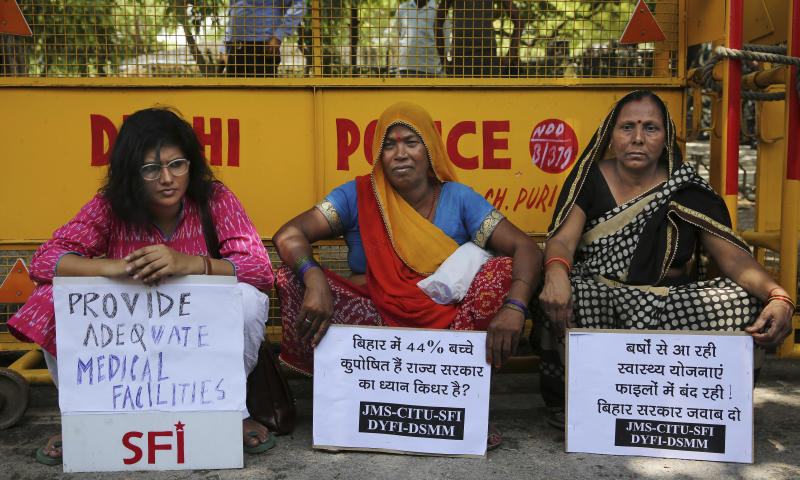 Left wing activists protesting against deaths of more than 100 children due to Encephalitis in the Indian state of Bihar, sit holding placards under a shade near a police barricade in New Delhi, India, Tuesday, June 18, 2019. (AP Photo/Altaf Qadri)