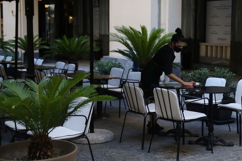 A waiter wearing a protective face mask sanitises a table at a coffee shop, amid the spread of the coronavirus disease (COVID-19), in Athens