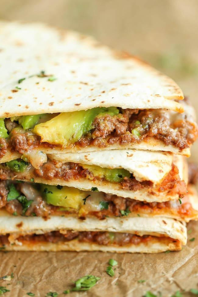 """<div><span>Per ½ quesadilla</span>: 219 calories, 11.5 g fat (4 g saturated), 452 mg sodium, 17.3 g carbs, 3 g fiber, < 1 g sugar, 12 g protein</div> Avocados are the perfect weight-loss food. According to research published in the journal <a rel=""""nofollow noopener"""" href=""""http://care.diabetesjournals.org/content/early/2010/04/23/dc09-2302?sid=069e131e-1884-40c2-a9ae-99be9067b607"""" target=""""_blank"""" data-ylk=""""slk:Diabetes Care"""" class=""""link rapid-noclick-resp""""><em>Diabetes Care</em></a>, a diet rich in monounsaturated fat can prevent abdominal body fat distribution by actually turning off certain fat genes. And that's not all—a study published in <a rel=""""nofollow noopener"""" href=""""https://nutritionj.biomedcentral.com/articles/10.1186/1475-2891-12-155"""" target=""""_blank"""" data-ylk=""""slk:Nutrition Journal"""" class=""""link rapid-noclick-resp""""><em>Nutrition Journal</em></a> found that participants who ate half a fresh avocado with lunch reported a 40 percent decreased appetite for up to hours afterward. That has us thinking about stuffing less cheese and more avocado into our quesadillas. <strong>Get the recipe from <a rel=""""nofollow noopener"""" href=""""http://damndelicious.net/2015/02/07/cheesy-avocado-quesadillas/"""" target=""""_blank"""" data-ylk=""""slk:Damn Delicious"""" class=""""link rapid-noclick-resp"""">Damn Delicious</a>.</strong>"""